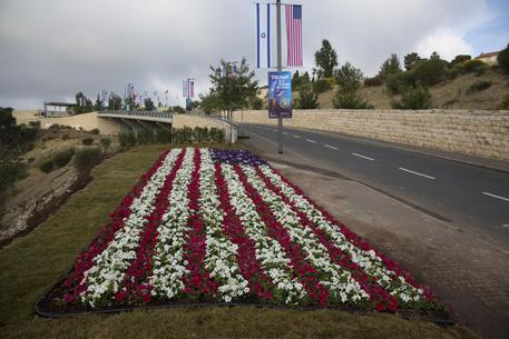 Flowers decorated as an American flag are seen on a road leading to the US Embassy compound ahead the official opening in Jerusalem, Sunday, May 13, 2018. On Monday, the United States moves its embassy in Israel from Tel Aviv to Jerusalem, the holy city at the explosive core of the Israeli-Palestinian conflict and claimed by both sides as a capital. The inauguration comes five months after President Donald Trump recognized Jerusalem as Israel's capital. (ANSA/AP Photo/Ariel Schalit) [CopyrightNotice: Copyright 2018 The Associated Press. All rights reserved.]