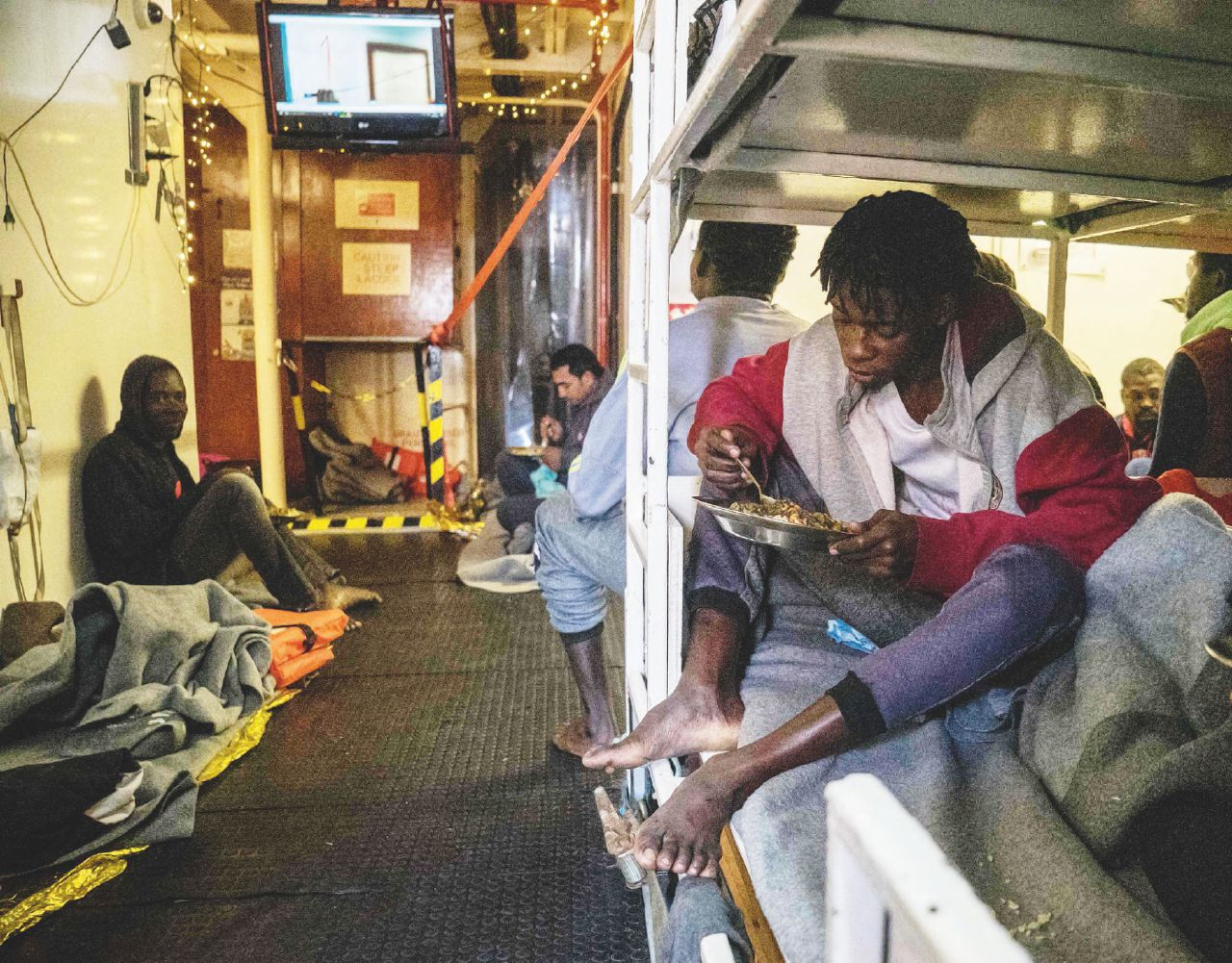 Rescued migrants eat a hot meal onboard the Dutch-flagged rescue vessel Sea Watch 3 on January 5, 2019, sailing the Mediterranean about 3 nautical miles off Malta's coast, a day after Mediterranea and Sea-Watch launched two boats to deliver supplies, including fresh water. - Thirty-two migrants, including children and teenagers rescued off Malta by a Sea-Watch rescue boat on December 22, 2018 remain at sea after being denied entry to European ports. The boat was given permission by Malta on January 3 to shelter off its coast due to a storm and fierce winds, but not to land. (Photo by FEDERICO SCOPPA / AFP)