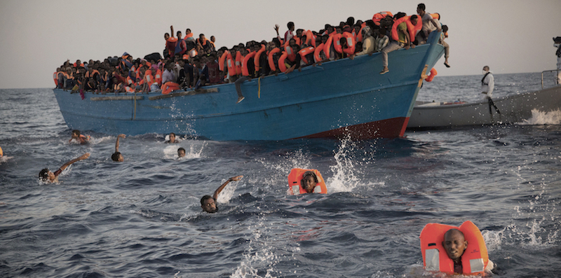 Alcuni migranti - soprattutto provenienti dall'Eritrea - si sono buttati in acqua da una barca sovraccarica, mentre altri vengono soccorsi da una ONG, a circa 20 chilometri da Sabrata, nel mar Mediterraneo (AP Photo/Emilio Morenatti)
