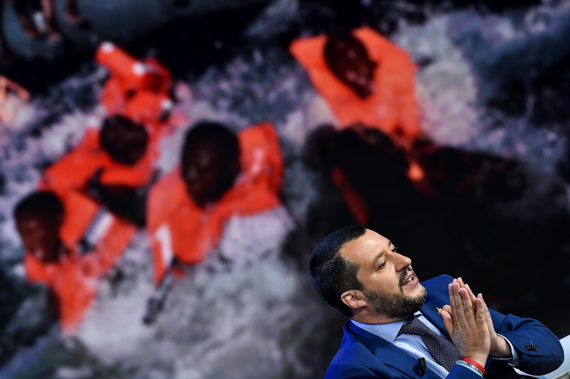 "TOPSHOT - Italy's Interior Minister and Deputy Prime Minister Matteo Salvini speaks during the Italian talk show ""Porta a Porta"", broadcast on Italian channel Rai 1, in Rome, on June 20, 2018, as picture of migrants is seen in the background. (Photo by Andreas SOLARO / AFP) (Photo credit should read ANDREAS SOLARO/AFP/Getty Images)"