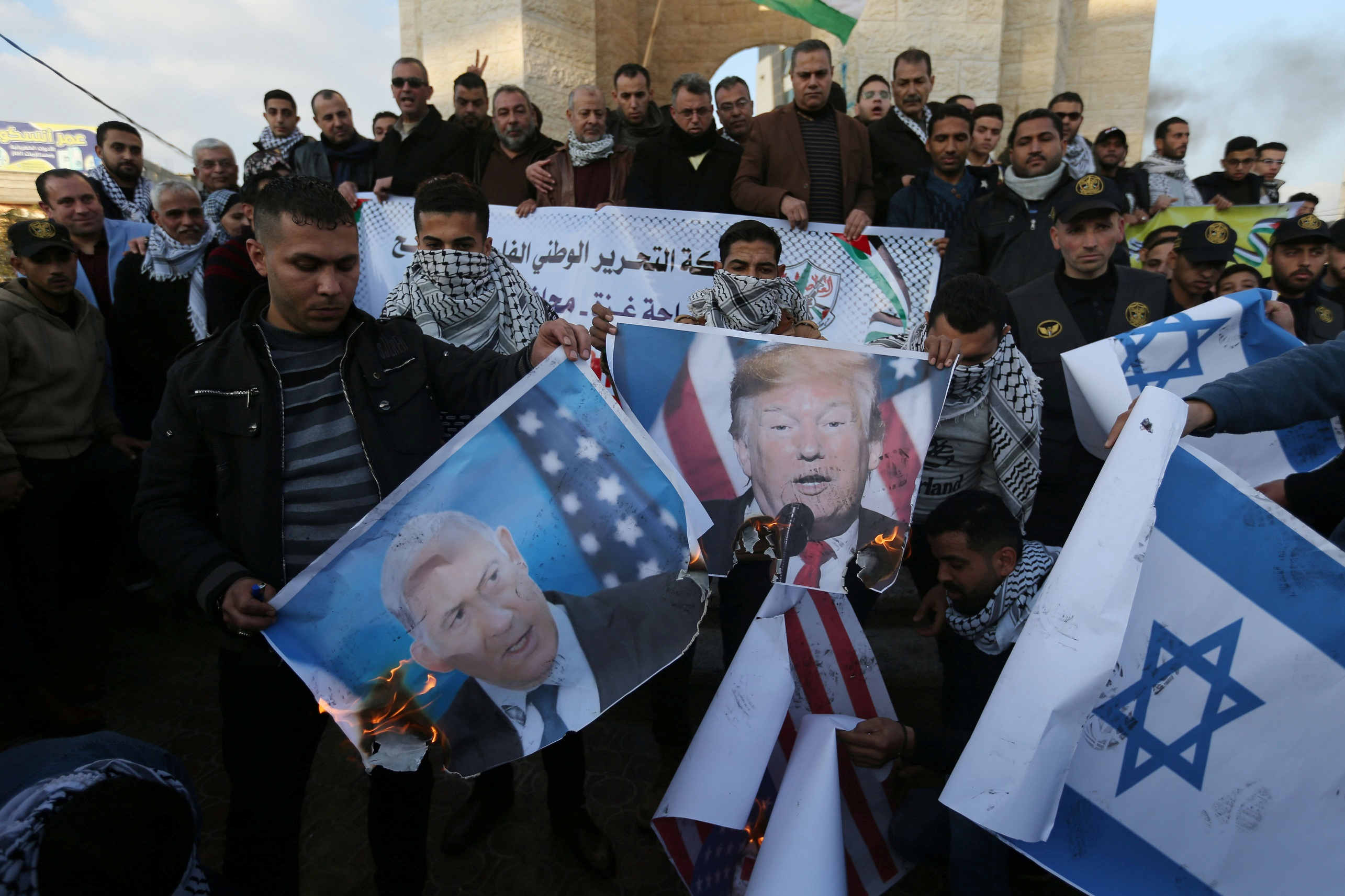 Palestinian demonstrators burn pictures depicting U.S. President Donald Trump and Israeli Prime Minister Benjamin Netanyahu, and repsentations of U.S and Israeli flags during a protest against the U.S. President Donald Trump's Middle East peace plan, in the southern Gaza Strip January 29, 2020. REUTERS/Ibraheem Abu Mustafa