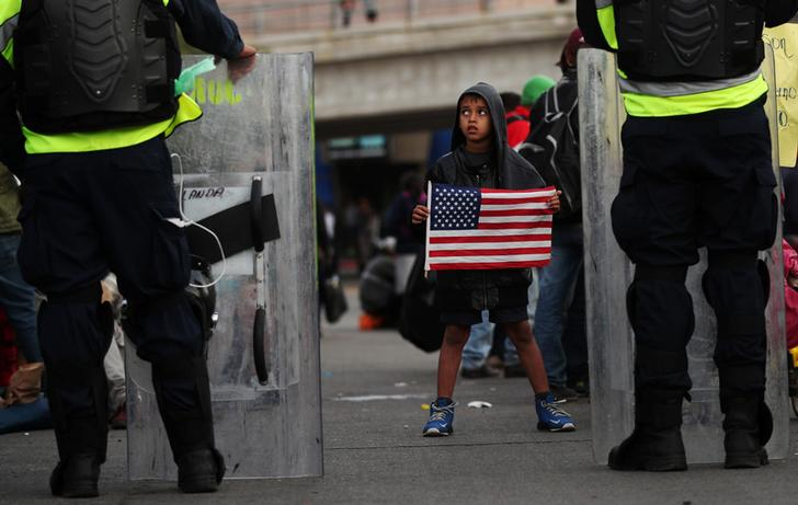 Michael Joel Miranda, an eight-year-old migrant boy from Honduras, part of a caravan of thousands from Central America trying to reach the United States, holds a U.S flag in front of Mexican riot police at the El Chaparral port of entry border crossing between Mexico and the United States, in Tijuana, Mexico, November 22, 2018. REUTERS/Hannah McKay