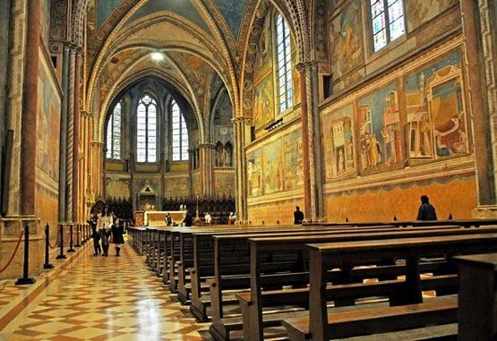 Eldorado, ad Assisi le porte della Basilica di San Francesco avvolte con coperte termiche per migranti