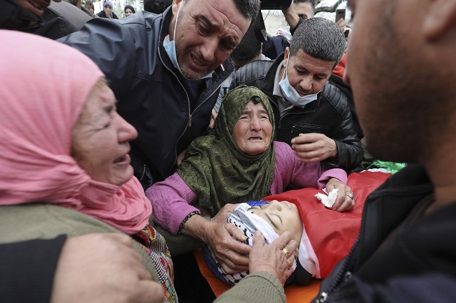 Relatives mourn during the funeral of Palestinian teenager Ali Abu Alia in the village of Mughayir near Ramallah in the Israeli-occupied West Bank, on December 5, 2020. - The Palestinian teenager was killed in clashes with the Israeli army on the sidelines of a protest in the occupied West Bank, the Palestinian health ministry said. (Photo by ABBAS MOMANI / AFP)
